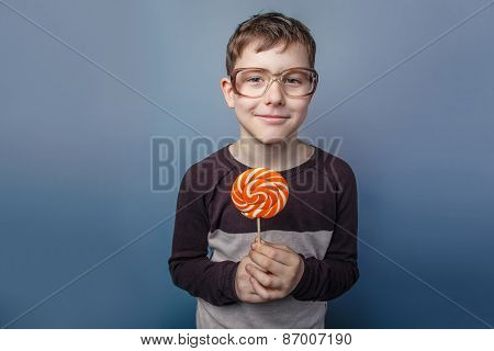 European-looking  boy  of  ten years in  glasses licking a lolli