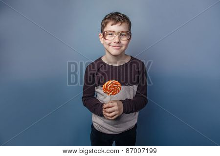 European-looking  boy  of ten years in  glasses licking a lollip