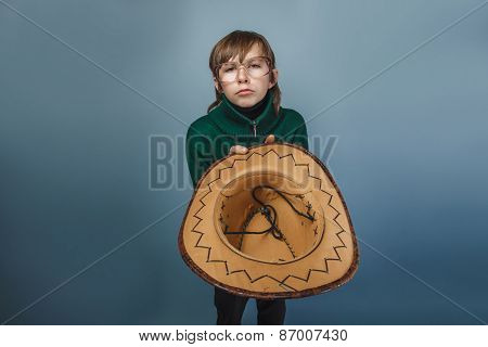 European-looking boy of ten years in glasses holding a hat, a be