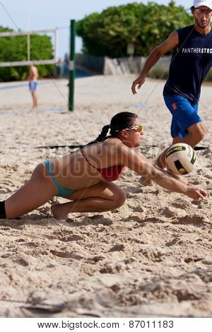 Young Woman Lunges To Reach Ball In Beach Volleyball Game