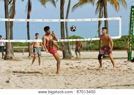Young Men Kick A Soccer Ball On Beach Volleyball Court