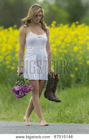A brunette model walks in a field of flowers