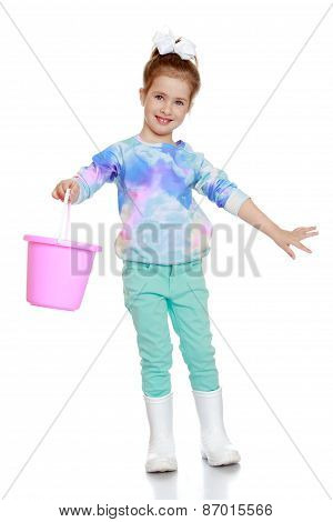 funny little girl in rubber boots and bucket in hand