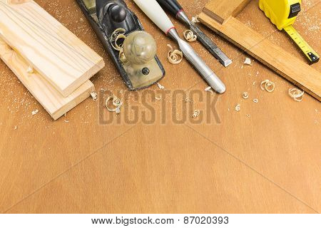 Chisels And Plane With Planks On Wooden Background