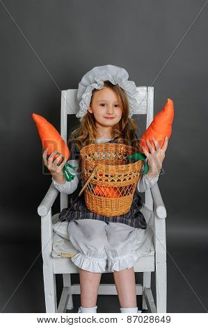 Girl With A Basket And Carrots On A Gray Background
