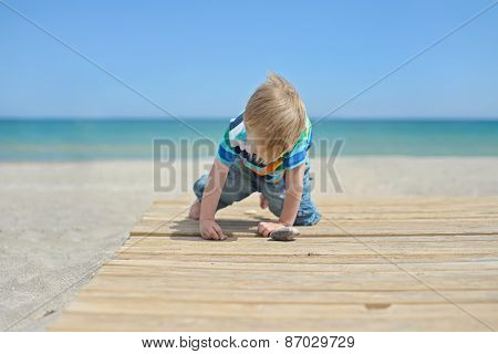 Small boy playing with stones on the beach