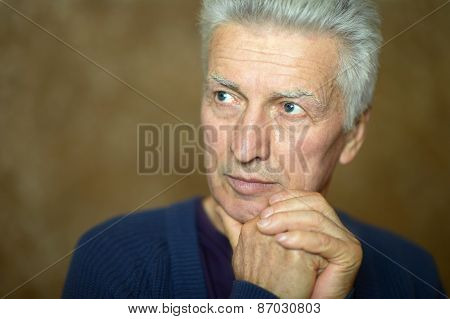 Pensive elderly man at home