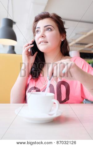 Beauty woman sitting in a cafe and talking on the cellphone