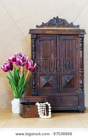 Bright Purple Flowers Tulips White Vase, Vintage Old Wardrobe And Wooden Chest With Pearls