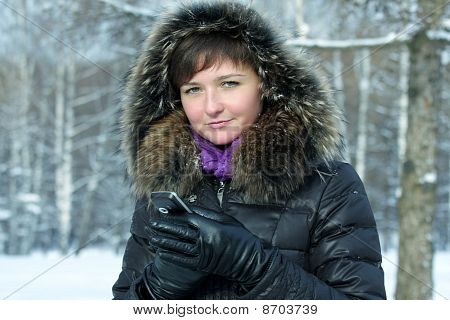 Cute Woman With Cellphone In Frosty Day