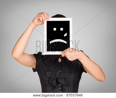 Girl in dress covered her face with tablet. On screen sad smiley