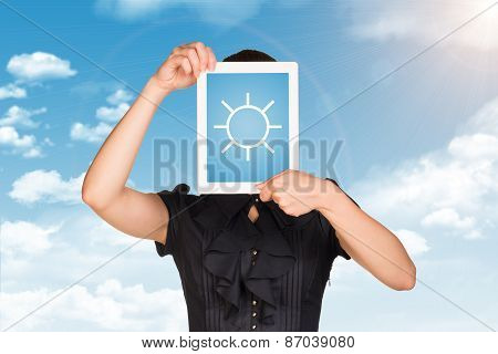 Girl in dress covered her face with tablet. On screen sun symbol