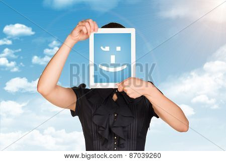 Girl in black dress covered her face with tablet. On screen code smiley