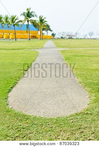 Concrete Pathway And Green Grass At Park