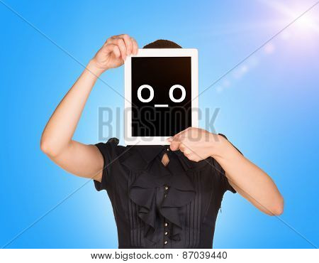 Young girl in black dress covered her face with tablet. On screen surprised smiley
