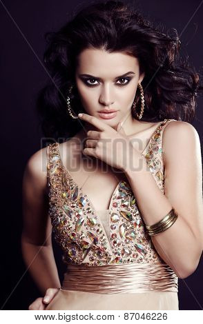 Sensual Woman With Dark Hair And Bright Makeup In Luxurious Sequin Dress