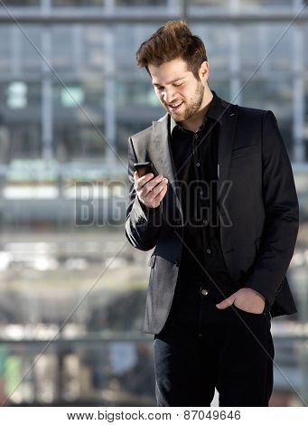 Handsome Young Man Looking At Mobile Phone Text Message