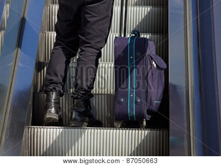 Man Standing On Escalator With Bag