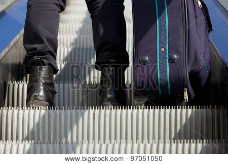 Man Standing On Escalator With Travel Bag