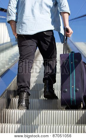 Back Of Man Walking Up Escalator With Travel Bag
