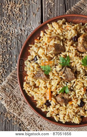 Pilaf traditional spicy asian food with rise, meat, onion, carrot and raisins
