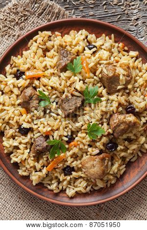 Pilaf is traditional delicious dish with fried meat, rise, carrot, onion and raisins