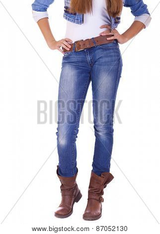 Front view of a standing woman model wearing denim with boots isolated on a white background