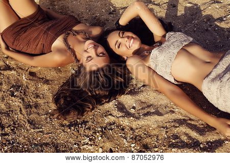 Photo Of Two Beautiful Girls With Dark Hair Lying On Beach