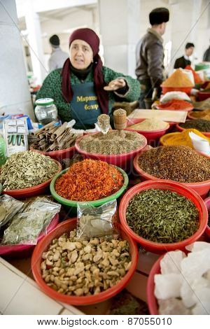 BUKHARA, UZBEKISTAN - MARCH 16, 2015: City grocery market. Woman sells nuts and dried fruits.