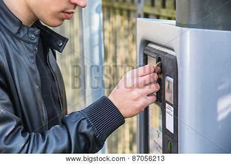 Young man paying for a parking ticket to be dispensed from booth