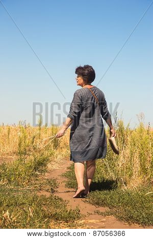 Barefooted Woman On Path Through Field