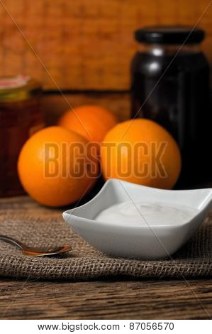 Bowl With White Yogurt On Jute Cloth And Spoon On Left