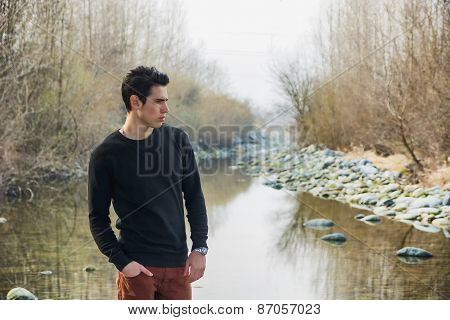 Attractive young man outdoor in nature, at river or water stream