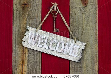 Welcome sign hanging on red wood rustic fence