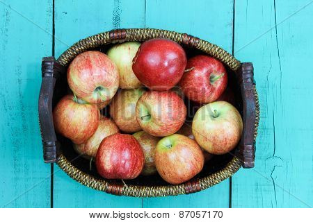 Basket of red apples sitting on wood table