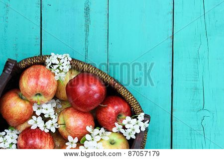 Basket with red apples and white spring flowers on wood table