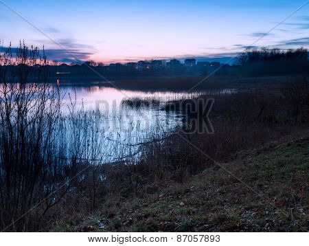 Beautiful Lake Near City With Colorful Sunset Sky. Tranquil Vibrant Landscape