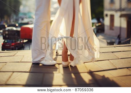 wedding legs of bride and groom on sunshine day