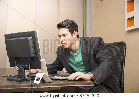 Serious handsome young businessman sitting at his desk