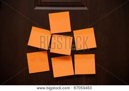 Seven blank sticky notes on the wooden door