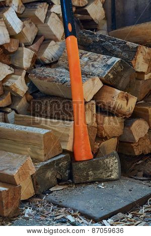 Axe With Black And Orange Handle And Firewood