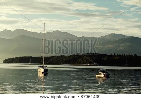 Yacht And Pleasure Boat At Sunset With Mountains In Kotor Bay, Montenegro