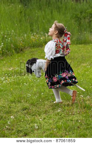 Little Girl Playing On A Meadow