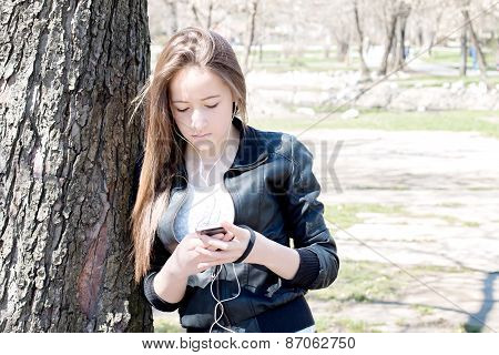 Young Girl With Smart Phone Leaning On The Old Big Tree
