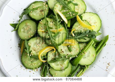 Green salad with cucumber, arugula and lemon peel, closeup