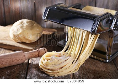 Making noodles with pasta machine on wooden background