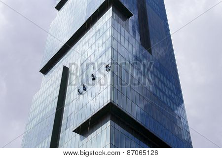 Group Of Workers Clean The Windows Of High Rise Modern Skyscraper As A Team In Downtown
