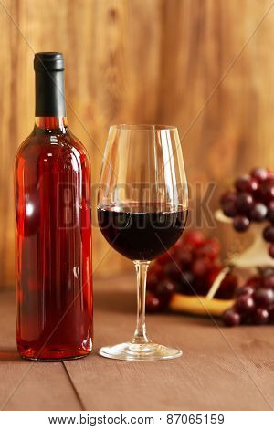 Bottle and glass of rose wine on wooden background