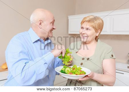 Couple holds a plate with salad