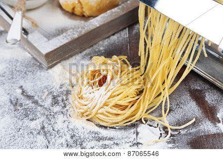 Making vermicelli with pasta machine and sprinkled flour on wooden background